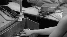 Девушка топлес играет на пианино