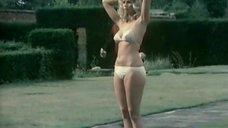 Девушка стоя загорает в купальнике