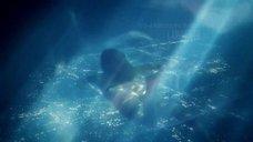Обнаженная девушка плавает в бассейне